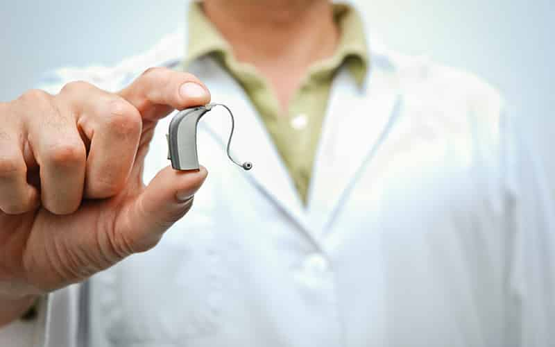 Audiologist holding hearing aid