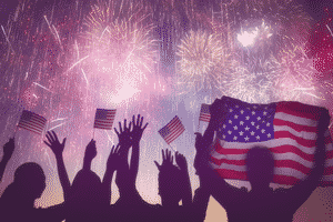 fireworks with silhouetted people and American flags